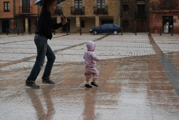 mom holding umbrellas with toddler in rain
